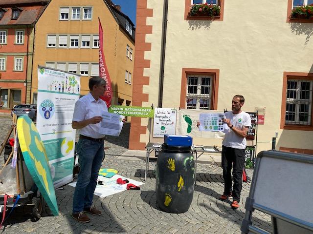 Stadtrat Thomas Vizl steht auf einem Stand vor dem alten Rathaus in Gerolzhofen und stellt die Klimawette vor.